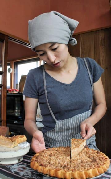 ビーガン食のアップルパイを切り分ける阿部さん
