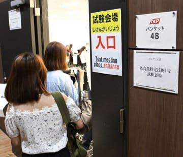 外食業分野の技能試験を受けるため試験会場に入る外国人=岡山市北区中山下