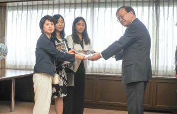 刑法改正を求めて小山刑事局長(右)に署名を提出する3団体の代表=東京都千代田区
