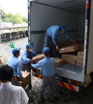 【投票用紙の入った箱をトラックに積み込む運送業者ら=三重県庁で】