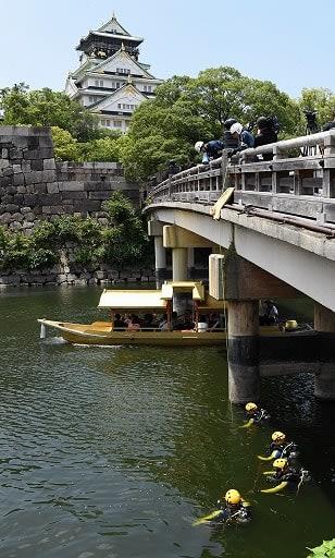 大阪城の内堀で不審物を捜索するダイバーら=24日、大阪市中央区