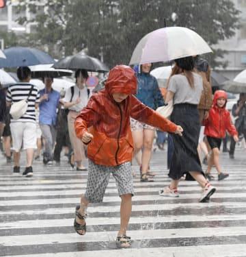 昨年7月、台風が近づく東京・渋谷の交差点を渡る子ども