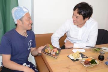 自慢の刺し身の盛り合わせを客に説明する魚谷さん(左)
