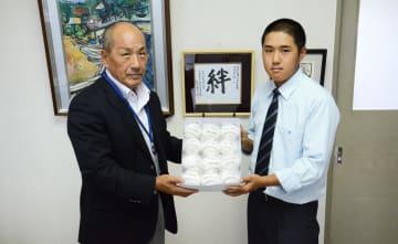 小山副会長(左)からボールを受け取る後藤主将