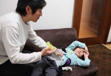 リラックスした様子の創志くん(右)と会話しながら、胃ろうを通じて水分を注入する金野大さん(左)=京都市北区の自宅