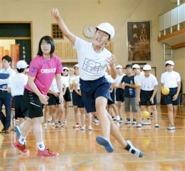 オムロンの選手からシュートを教わる長嶺小の児童=熊本市東区