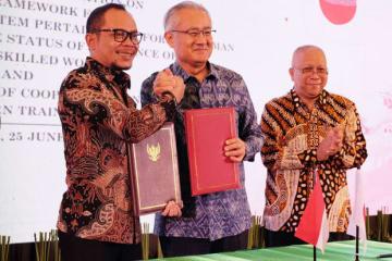特定技能に関する協力覚書に署名したハニフ労相(左)と石井大使(中央)=25日、ジャカルタ(在インドネシア日本大使館提供)
