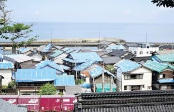 瓦の落下した屋根にビニールシートを張った家が目立つ鶴岡市温海地区の小岩川集落=25日