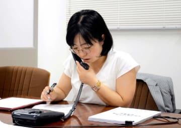 女性からの電話相談に応じる弁護士=25日午後、松山市三番町4丁目