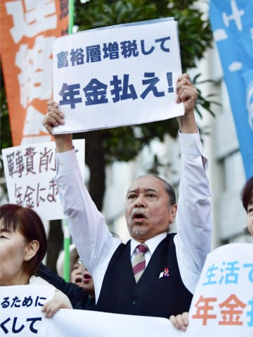 抗議集会で、「年金払え」と書かれた紙を掲げる男性=26日午後、首相官邸前