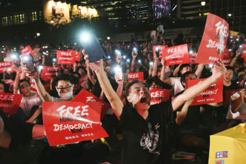 香港中心部で開かれた民主派団体の集会で声を上げる参加者=26日(共同)