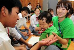 そっと赤ちゃんの手に触れる生徒=富士中学校