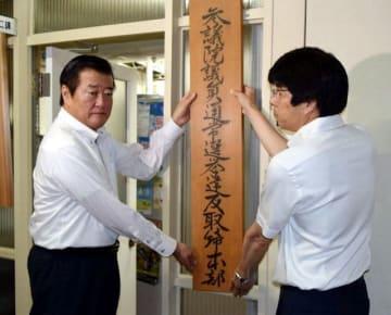 選挙違反取締本部の看板を設置する間野刑事部長(左)ら