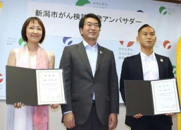 新潟市のがん検診啓発アンバサダーに任命された伊勢みずほさん(左)、早川史哉さん(右)と中原八一市長=26日、市役所