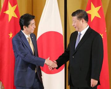中国の習近平国家主席(右)と握手する安倍首相=27日午後、大阪市内のホテル(代表撮影)