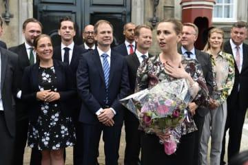 花束を手に宮殿前へ登場したデンマークのフレデリクセン新首相=27日、コペンハーゲン(AP=共同)