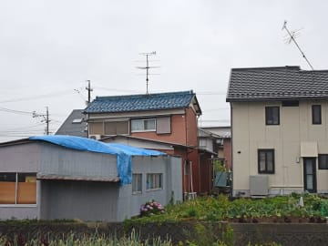 突風で屋根が飛び、ブルーシートがかぶせられた物置(左手前)=27日午後6時30分、岐阜市手力町
