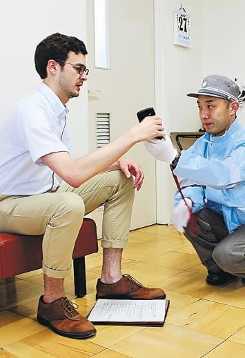 レイモスさん(左)に携帯電話を渡して話してもらい、通訳を介して状況を把握する救急隊員