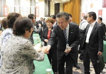 自民党県連が開いた選対本部会議の終了後、友好団体の関係者と握手する馬場成志氏=22日、熊本市中央区