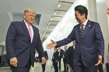 トランプ米大統領(左)を出迎える安倍首相=28日午前、大阪市(AP=共同)