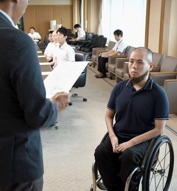 強化指定証を受け取る乗松聖矢選手(右)=県庁