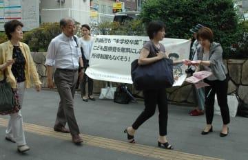 請願の提出前に、街頭で小児医療費助成拡大を訴えるメンバーら=川崎市役所前