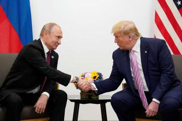 28日、大阪で会談した際に握手するロシアのプーチン大統領(左)と米国のトランプ大統領(ロイター=共同)