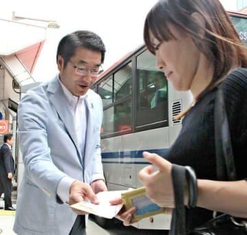 古町バス停でアンケート用紙を配る中原八一市長=27日、新潟市中央区