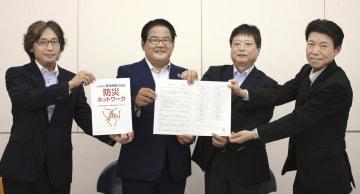 災害時の相互協力に関する協定書を手にする、日本コミュニティ放送協会東海地区協議会の久田五海会長(左から3人目)ら=28日午後、名古屋市