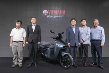 Masashi Ogawa (C), president of Yamaha Motor Taiwan Co., stands next to the EC-05 electric scooter, designed by Yamaha Motor Co. and modeled after a Gogoro production vehicle, in Taipei on June 27, 2019.(Courtesy of Yamaha Motor Co.)