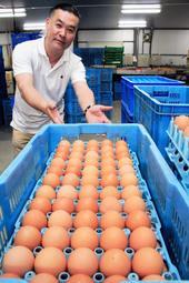 市川町のPRに一役買っている田隅養鶏場の卵と従業員の倉元敏美さん=市川町田中