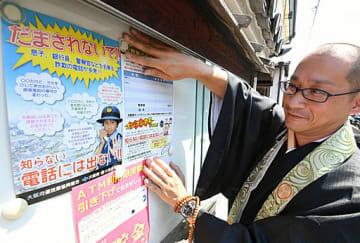掲示板に特殊詐欺被害防止のチラシを貼り、注意を呼び掛ける河合さん=堺市堺区