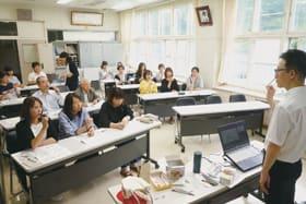 有江さん(右)の指導でお菓子を使って母音の教え方を実践する参加者