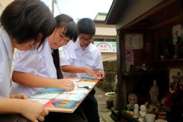 地蔵堂の前で天井絵の張り替え作業をする生徒=長崎市万才町