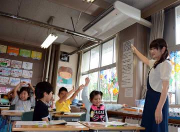 手を上げてエアコンの冷たい風を感じる児童