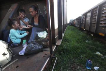 貨物列車に乗る移民の親子=24日、メキシコ南部チアパス州(AP=共同)