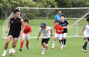子どもたちとサッカーを楽しむ香川真司選手(左)