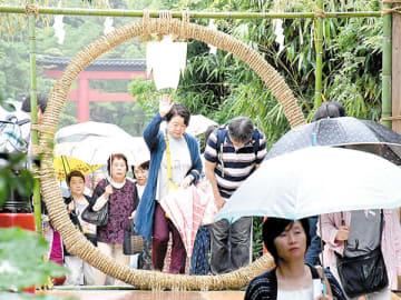 傘を手に茅の輪をくぐり無病息災を願う参拝者たち=29日午前、さいたま市大宮区の氷川神社