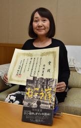 日本児童文学者協会賞を受賞した著書「むこう岸」と安田夏菜さん=川西市役所