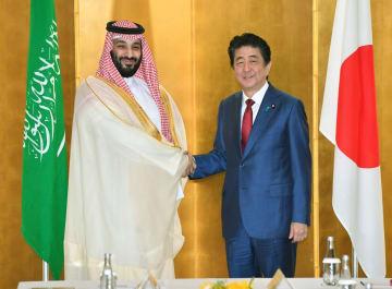 会談を前に握手を交わすサウジアラビアのムハンマド皇太子(左)と安倍首相=30日午前、大阪市内のホテル(代表撮影)