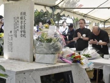 米軍戦闘機が墜落した事故から60年となり、犠牲者の名前が刻まれた石碑に手を合わせる沖縄県の玉城デニー知事(右から2人目)ら=30日午前、沖縄県うるま市の宮森小