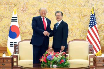 会談を前に握手するトランプ米大統領(左)と韓国の文在寅大統領=30日、ソウルの韓国大統領府(聯合=共同)