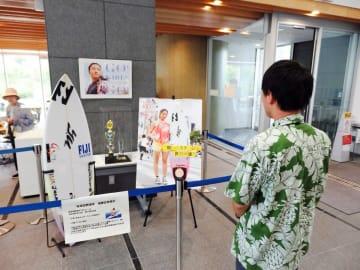 松田さんが大会で使ったサーフボードなどが並ぶ記念展示=茅ケ崎市役所