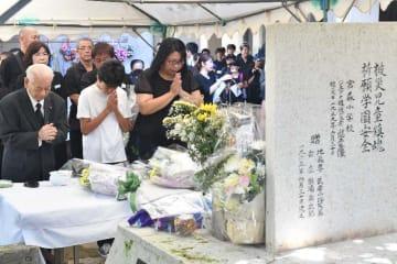 仲よし地蔵に礼拝し、犠牲者を追悼する出席者=30日午前9時34分、うるま市石川・宮森小学校