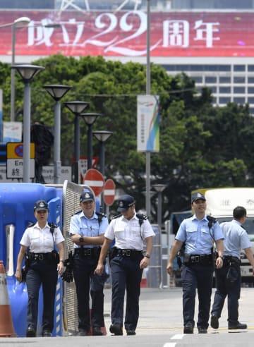 香港返還22年を前に、中国国旗の掲揚式典が行われる会場周辺で警備する警官隊=30日、香港(共同)