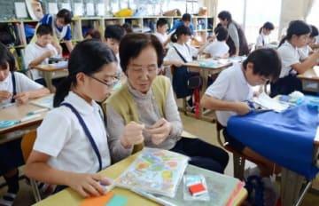 家庭科の授業で一緒に裁縫をする児童とお年寄り=霧島市溝辺の陵南小学校