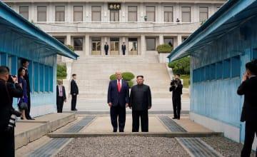 6月30日、板門店の北朝鮮側に立つトランプ米大統領(左)と金正恩朝鮮労働党委員長(ロイター=共同)