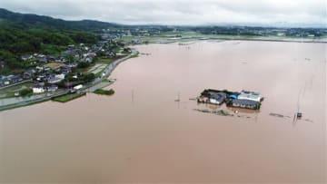 大雨の影響で木山川などが氾濫し、浸水した益城町赤井付近の田んぼ。左は国道443号=30日午後2時すぎ(高見伸、小型無人機で撮影)