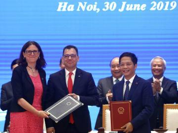 ベトナムとのFTAに調印したEUのマルムストローム欧州委員(左)とベトナムのチャン・トゥアン・アイン商工相(右)ら=6月30日、ハノイ(ロイター=共同)
