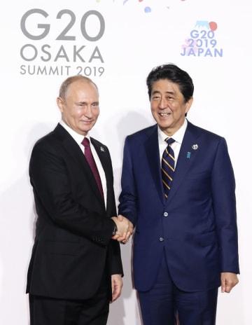G20大阪サミットでロシアのプーチン大統領(左)を迎え、握手する安倍首相=6月28日午前、大阪市(代表撮影)